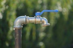 An outdoor faucet in the garden stock photo