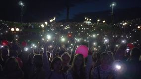 Outdoor festival, crowd fans with flashlights on smartphone waving hands and enjoy live music during night concert on