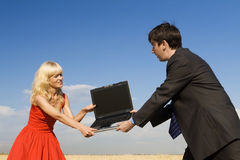 Outdoor fighting. Businessman and lady in red fighting for notebook Royalty Free Stock Image