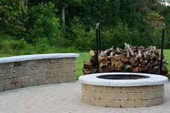 Outdoor Fire Pit. An outdoor fire pit, built of stone blocks and concrete, sits in the middle of a stone patio, with a curved stone bench and a large stack of Royalty Free Stock Image