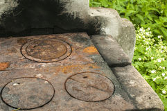 Outdoor fireplace detail. Outdoor rustic fireplace with weathered rusted cast iron grill plate stock photo
