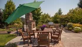 Outdoor fireplace and kitchen area with umbrella. A garden, a large stone fireplace a luxury BBQ and seating makes this a perfect entertaining area for both Stock Photography