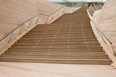 Outdoor flight of stairs. Made of wooden slats with pair of inward leaning stainless steel railings adding an elegant touch to the modern design Stock Photo
