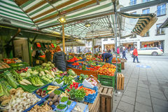 Outdoor food market in Munich. MUNICH, GERMANY - MAY 9, 2017 : People buying fruit and vegetable at the outdoor food market near Marienplatz in Munich, Germany Stock Image