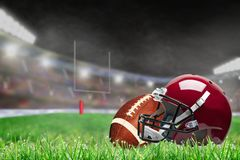 Outdoor Football Stadium With Helmet and Ball and Copy Space. American football helmet and ball on field grass in brightly lit outdoor stadium with focus on stock photo