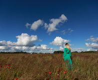 Outdoor freedom. Relax of the girl in the field with poppies Royalty Free Stock Photo