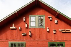 Outdoor front view of many bird nest boxes on red exterior wooden building wall with windows. Horizontal composition stock photography