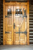 Outdoor front view of a naturally wood finished door entrance. Rustic traditional decorative pattern with iron hinge fittings. Vertical composition royalty free stock photos