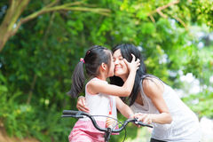 Outdoor fun. Asian child kissing her mother. Asian family having fun outdoor, biking outdoor stock images