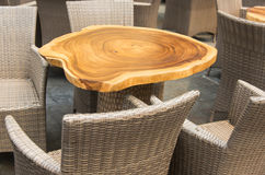Outdoor Furniture. Wicker arm chair and natural wood table top outdoor furniture Royalty Free Stock Photos