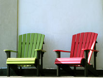 Outdoor Furniture Adirondack Chairs on House Porch. Two bright color red and green outdoor furniture Adirondack resin chairs on a country house porch Stock Images