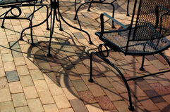 Outdoor furniture on a brick patio. Outdoor furniture casts shadows on a brick patio stock images