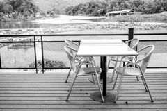 Outdoor furniture set in black and white. Outdoor furniture including four stainless chairs and a stainless table on wooden floor. For leisure and having meal stock photo
