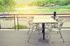 Outdoor furniture set. Outdoor furniture including four stainless chairs and a stainless table on wooden floor. For leisure and having meal. Background is nature royalty free stock image