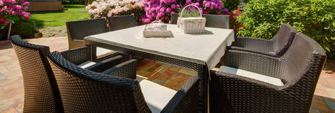 Outdoor furniture set. Panorama of outdoor furniture set and wicker picnic kit Royalty Free Stock Photos