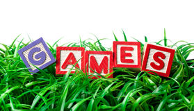 Outdoor games. Alphabet blocks forming GAMES on a patch of grass Royalty Free Stock Images