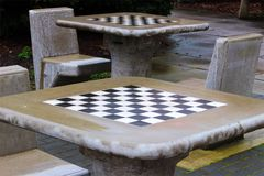 Abandoned outdoor chess tables on a wet Spring morning, Norfolk UK. Outdoor games area after an April shower. Chequered concrete chess tables and chairs slowly Royalty Free Stock Photo