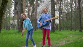 Outdoor games of childrens, cheerful girlfriends jointly jump with guitar in hand into the park in springtime. In warm season stock video footage