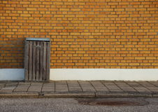 Outdoor Garbage Can with Yellow Brick Wall Background Stock Photography