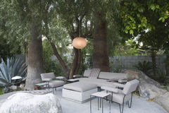 Outdoor Garden Furniture. View of circular lamp over outdoor garden furniture by trees Stock Photography