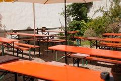 Outdoor garden restaurant. Sunny outdoor simple restaurant with orange bench Royalty Free Stock Photography