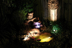 Outdoor garden with water feature fishpond at nigh. Outdoor water feature fishpond with fountain in garden at night Royalty Free Stock Photography