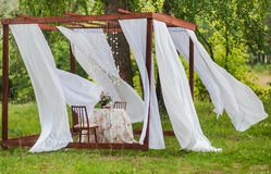 Outdoor gazebo with white curtains. Wedding decorations. Royalty Free Stock Photo