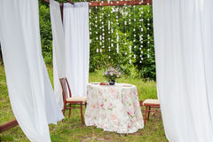 Outdoor gazebo with white curtains. Wedding decorations. Royalty Free Stock Image
