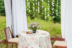 Outdoor gazebo with white curtains. Wedding decorations. Stock Photo