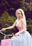 Outdoor glamour portrait of a sexy blonde girl riding a bicycle in the park Royalty Free Stock Photography