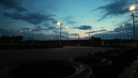 Outdoor go-kart track with cars passing under dark blue evening sky, time-lapse. Stock footage stock video footage