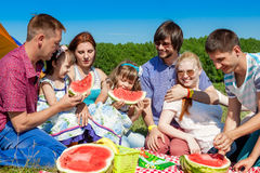 Outdoor group portrait of happy company having picnic on green grass in park and enjoying watermelon Stock Photos