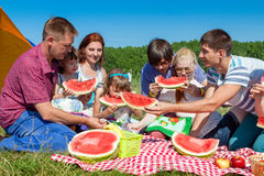 Outdoor group portrait of happy company having picnic near the tent in park and enjoying watermelon Stock Photos