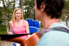 Outdoor Guitar. A man playing a guitar outdoors for a girl royalty free stock images