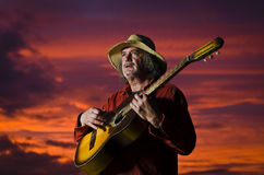 Outdoor guitarist with surreal sunset Royalty Free Stock Image