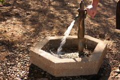 Outdoor hand-pumped faucet. Is being pumped, causing the water to flow from a well located in the country Stock Photos