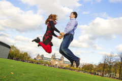 Outdoor happy couple jumping in Museumplein, Amsterdam Royalty Free Stock Image