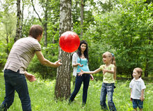 Outdoor happy family plaing ball . Royalty Free Stock Photo