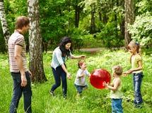 Outdoor happy family plaing ball . Royalty Free Stock Photo