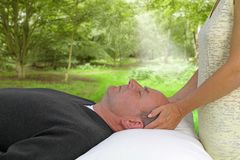 Outdoor healing session, soft blur background. Female healer channeling healing to male client during outdoor healing session Stock Images