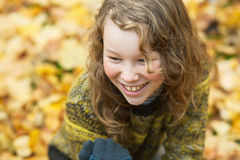 Outdoor high angle portrait of smiling blond girl. In autumn park Stock Images