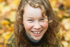 Outdoor high angle portrait of smiling blond girl. In autumn park Stock Photo