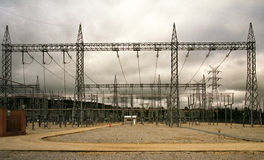 Outdoor high voltage substation with steel gantry and grey sky Royalty Free Stock Images
