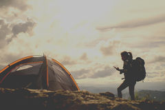 Outdoor hiker concept. Girl hiker and a tent and holding a mobile phone check GPS mountains in the background Stock Photography