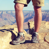Outdoor hiking shoes - legs of male hiker walking. Outdoor hiking shoes - closeup crop of legs of male hiker walking in wool socks and boots on summer nature Royalty Free Stock Photography