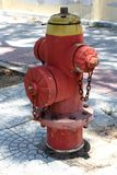 Fire hydrant. Red fire equipment with yellow cap and chain. royalty free stock photography