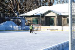 Outdoor ice hockey rink in late afternoon with single skater royalty free stock image