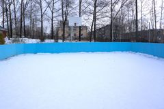 An outdoor ice skating rink and a hockey net with tall frost covered trees in the background in a winter landscape.  Royalty Free Stock Image