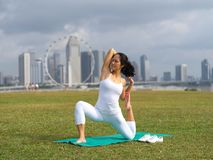 Asian chinese woman practising yoga outdoors in Singapore. Outdoor image of an asian chinese woman practising yoga with the landscape of singapore in the Royalty Free Stock Photo