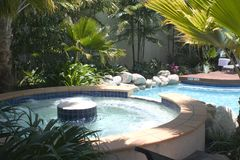 Outdoor Jacuzzi. Tropical outdoor jaccuzzi next to outdoor hotel pool Royalty Free Stock Photography